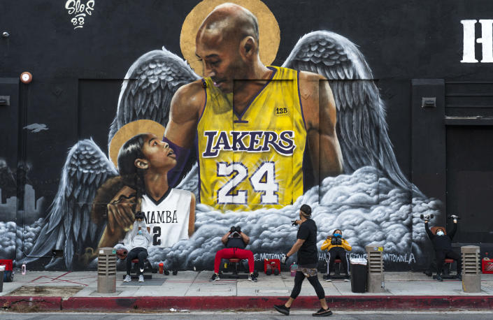 People lift weights on a sidewalk outside the Hardcore Fitness gym, due to COVID-19 restrictions, under a mural honoring NBA star Kobe Bryant and his daughter Gigi near Staples Center in downtown Los Angeles, Monday, Jan. 25, 2021. Bryant, who became one of the greatest basketball players of his generation during a 20-year career with the Lakers, died in a helicopter crash with his daughter Gigi and other passengers on Sunday, Jan. 26, 2020. (AP Photo/Damian Dovarganes)