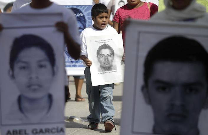 A child takes part in a protest to demand the safe return of 43 students who went missing in southern Mexico, on November 13, 2014 (AFP Photo/Pedro Pardo)