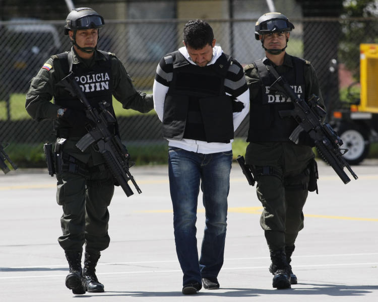 Alleged drug trafficker Juan Carlos Calle Serna, center, is escorted by police in handcuffs and body armor after being deported from Ecuador, at a police station in Bogota, Colombia, Sunday March 18, 2012. Calle Serna was captured in Quito, Ecuador on Friday. (AP Photo/Nestor Silva)