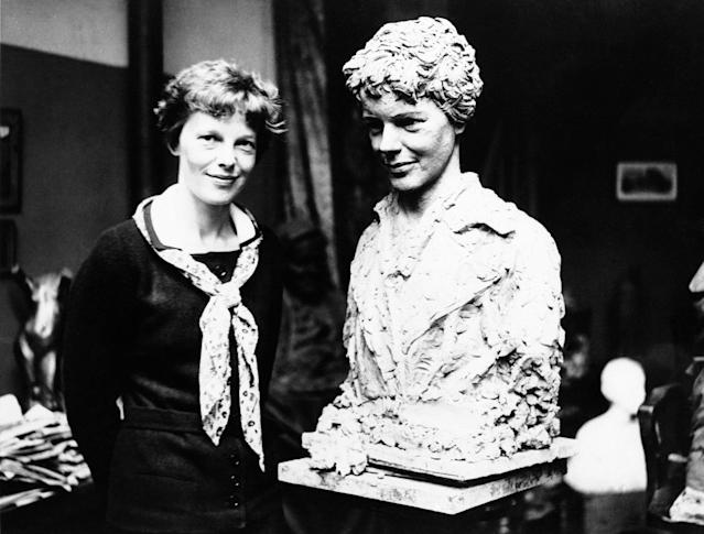 Mrs. Amelia Earhart Putnam pictured beside a likeness of herself executed by George Conlon, an American sculptor now living in Paris in an undated photo. The bust which is remarkable facsimile of the transatlantic flier was modeled almost entirely with the aid of photographs because of the inability of the flier to devote most of her time while in Paris to the sittings. (AP Photo)