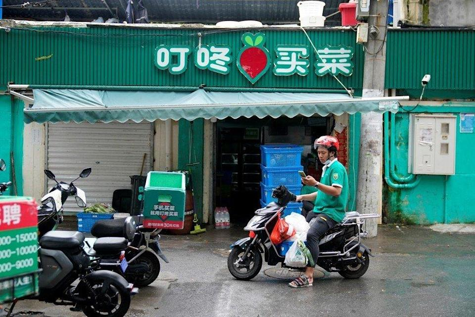 A delivery worker for Chinese online grocery Dingdong Maicai on a street in Shanghai on June 2021. Photo: Reuters.