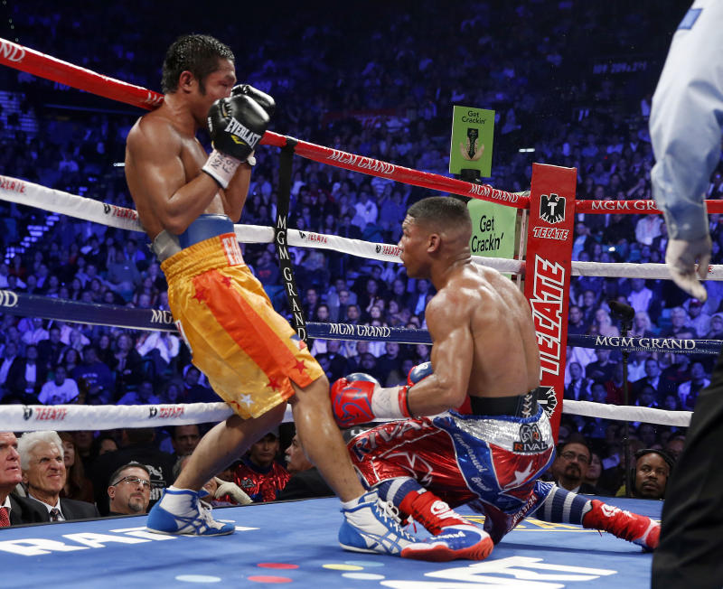 Michael Farenas, from the Philippines, left, sends Yuriorkis Gamboa, from Miami, Fla., to the canvas in the ninth round during their WBA interim super featherweight title fight Saturday, Dec. 8, 2012, in Las Vegas. (AP Photo/Eric Jamison)