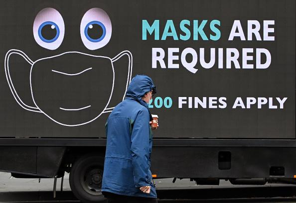 A man walks past a sign on a truck in Melbourne on as the city enforces strict lockdown restrictions after a fresh outbreak of the COVID-19 coronavirus.