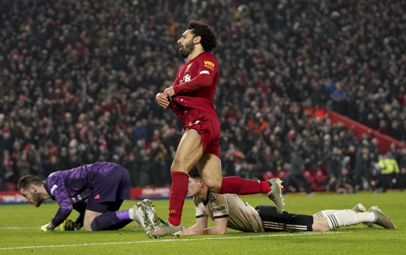 Liverpool's Mohamed Salah, centre, celebrates after scoring his side's second goal during the English Premier League soccer match between Liverpool and Manchester United at Anfield Stadium in Liverpool, Sunday, Jan. 19, 2020.(AP Photo/Jon Super)
