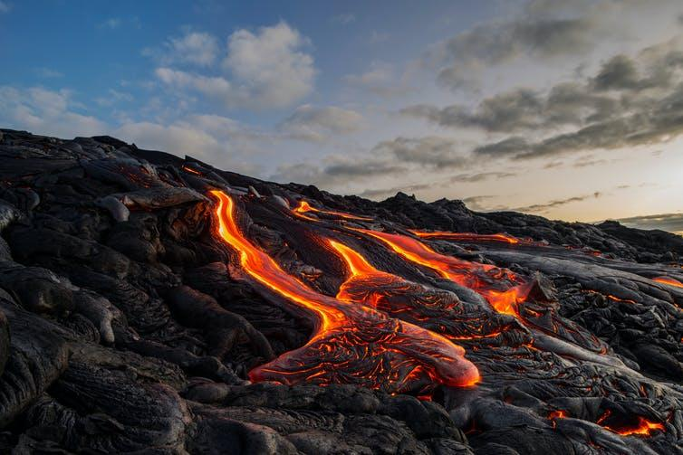 Molten lava flowing down hill of solidified lava