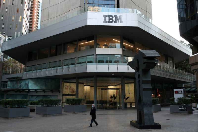 FILE PHOTO: A man wearing a protective mask walks past an office building with IBM logo amidst the easing of the coronavirus disease (COVID-19) restrictions in Sydney