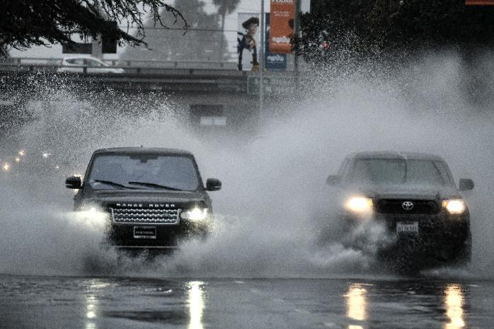 Cars barrel their way through a flooded street in the Van Nuys section of Los Angeles on Sunday, Jan. 22, 2017. California residents evacuated neighborhoods below hillsides scarred by wildfires as the third, and largest, in the latest series of storms brought powerful rain Sunday and warnings about flash flooding and mudslides. (AP Photo/Richard Vogel)