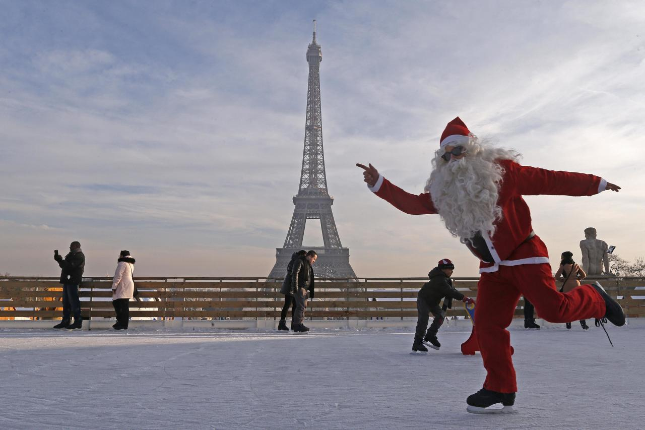 A man dressed as Santa Claus skates on an ice rink across from the Eiffel Tower as part of the Christmas holiday season preparations, in Paris December 12, 2013. REUTERS/Jacky Naegelen (FRANCE - Tags: SOCIETY TRAVEL TPX IMAGES OF THE DAY)