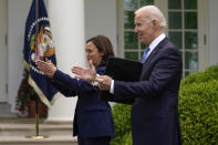 President Joe Biden claps with Vice President Kamala Harris after speaking on updated guidance on face mask mandates and COVID-19 response, in the Rose Garden of the White House, Thursday, May 13, 2021, in Washington. (AP Photo/Evan Vucci)