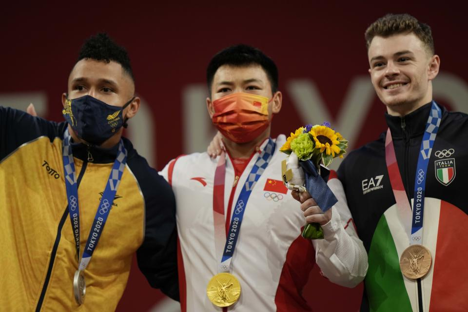 Gold medalist Chen Lijun of China, center, stands with silver medalist Javier Luis Masquera Lozano of Colombia, left, and bronze medalist Mirko Zanni of Italy, right, after the men's 67kg weightlifting event, at the 2020 Summer Olympics, Sunday, July 25, 2021, in Tokyo, Japan. (AP Photo/Luca Bruno)