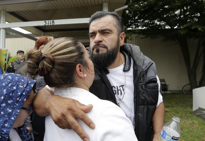 Jose Robles embraces his wife, Susana Robles, after leaving Riverton Park United Methodist Church before walking to present himself to U.S. Immigration and Customs Enforcement officials Wednesday, July 17, 2019, in Tukwila, Wash. Robles, who has spent the past year inside a Seattle church to avoid being deported to Mexico, has been detained. The arrest Wednesday prompted protests from a crowd of supporters who had accompanied Robles to the agency. His deportation has temporarily been put on hold by a federal appeals court, and he has a pending visa application. (AP Photo/Elaine Thompson)