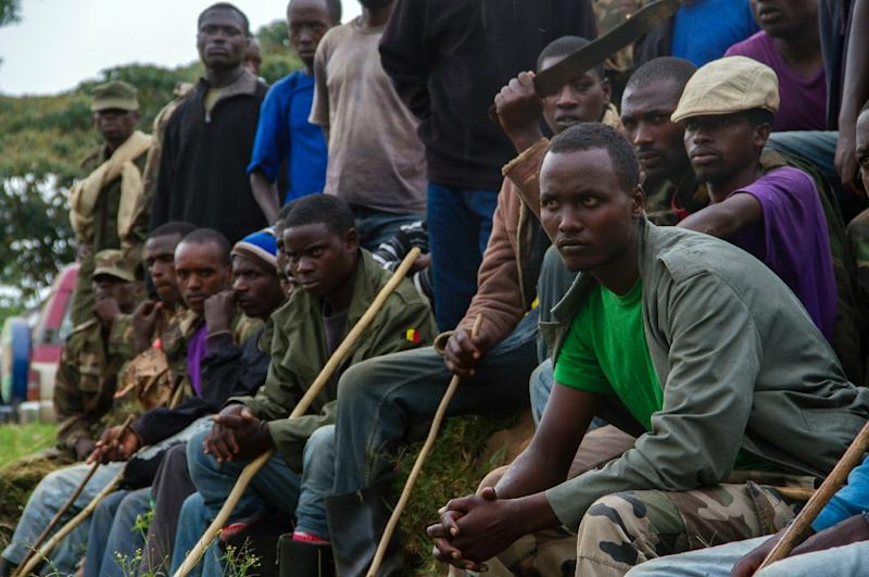 Members of the Democratic Republic of Congo rebel group M23 sit at the refugee settlement in Ramwanja, Uganda on December 17, 2014