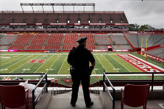 A police officer looks out on a wet field at Rutgers football stadium before an NCAA college football game between Rutgers and Penn State, Saturday, Sept. 13, 2014, in Piscataway, N.J. (AP Photo/Mel Evans)