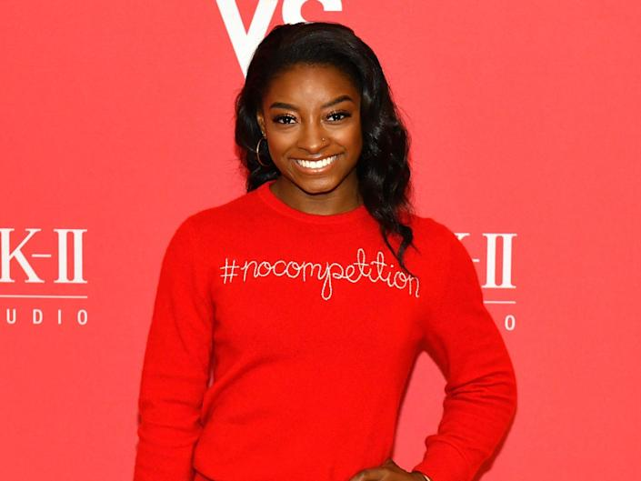 simone biles poses on a red carpet