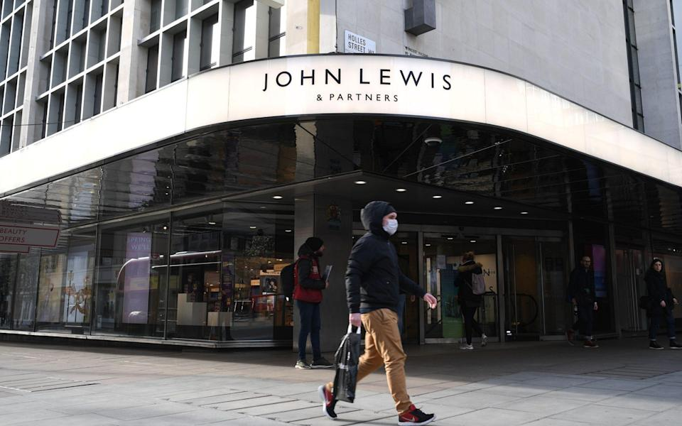 A man wearing a protective face mask walks past the front entrance of John Lewis department store on Oxford Street in central London - DANIEL LEAL-OLIVAS/AFP