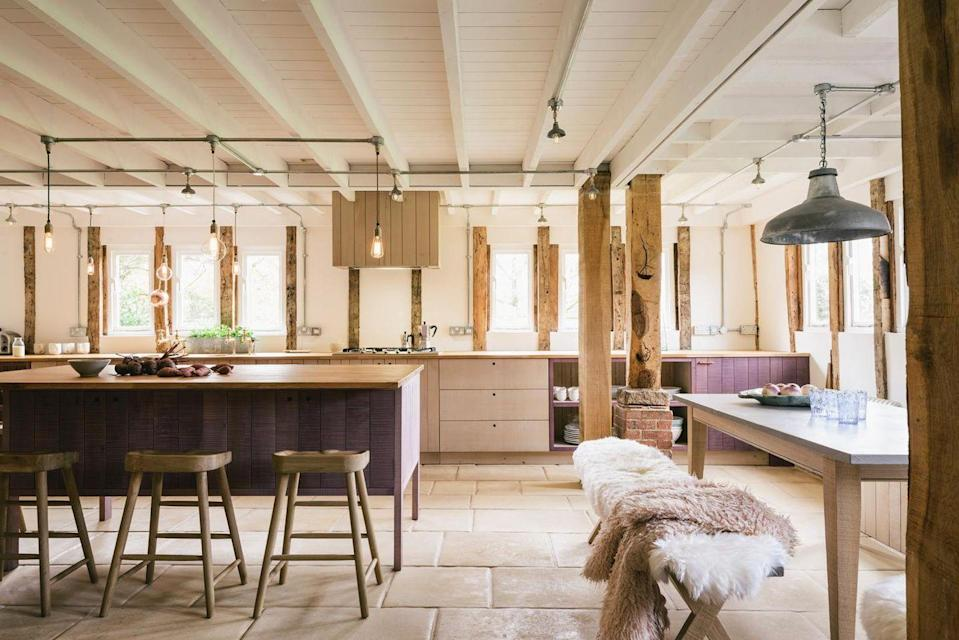 <p>If you prefer the look of unpainted wood but also like to play with colors, consider dyeing your wood cabinets a unique color. In this deVOL kitchen, the aubergine island and lower corner cabinet is super unexpected. We're also loving all the exposed beams and casual floor tiling. </p>