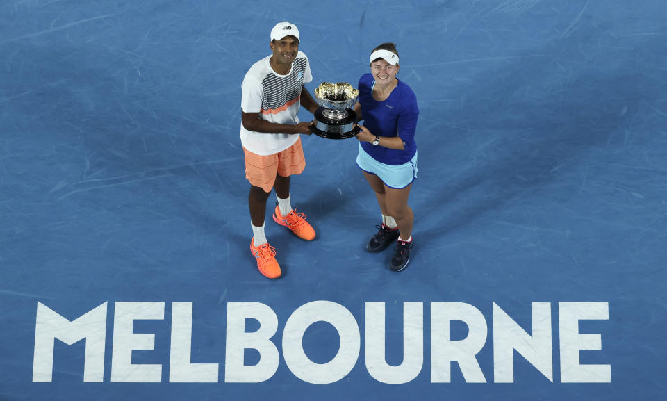 Rajeev Ram of the US and Barbora Krejcikova of the Czech Republic pose with their trophy after defeating Australia's Samantha Stosur and Matthew Ebden in the mixed doubles final at the Australian Open tennis championship in Melbourne, Australia, Saturday, Feb. 20, 2021.(AP Photo/Hamish Blair)