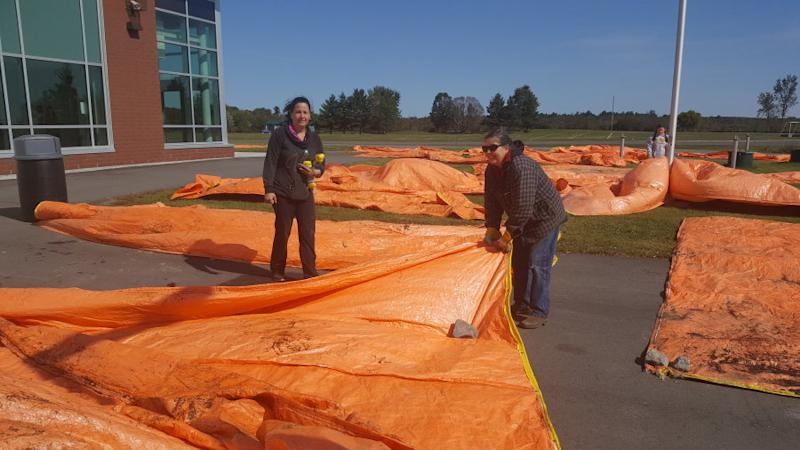 Kara McShaw Plourde (left) donated tarps for Dunrobin residents to use to protect their homes from expected rain.