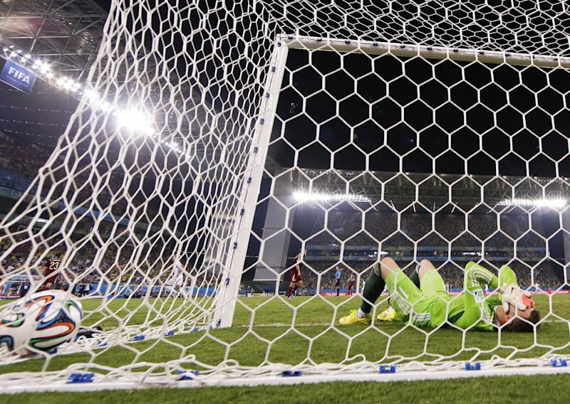 Russia's goalkeeper Igor Akinfeev covers his face after dropping the ball as South Korea's Lee Keun-ho scores the opening goal during the group H World Cup soccer match between Russia and South Korea at the Arena Pantanal in Cuiaba, Brazil, Tuesday, June 17, 2014