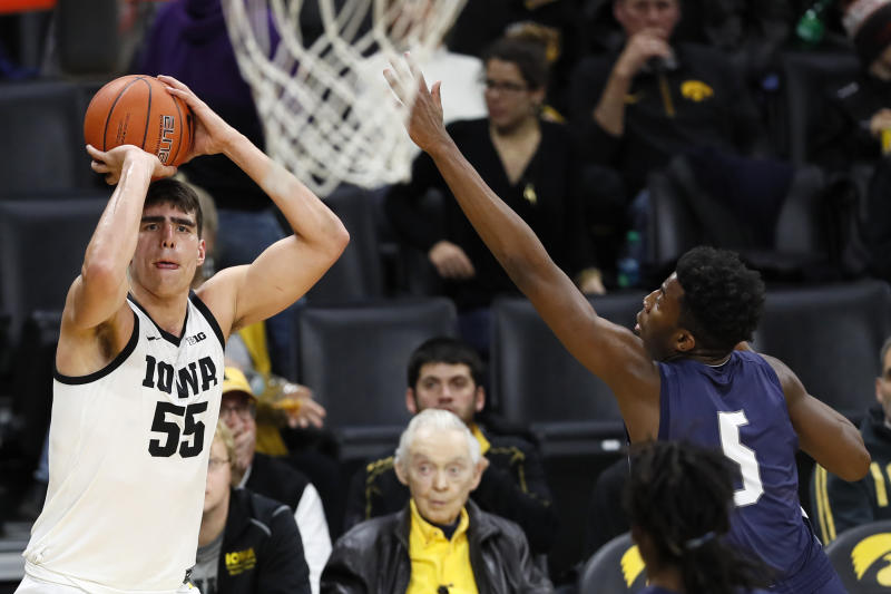 Iowa center Luka Garza, left, shoots a three-point basket ahead of North Florida forward Dorian James (5) during the second half of an NCAA college basketball game, Thursday, Nov. 21, 2019, in Iowa City, Iowa. (AP Photo/Charlie Neibergall)