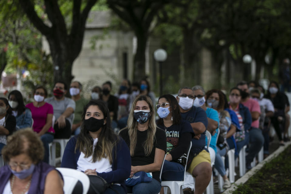 People wear masks during Mass amid the new coronavirus pandemic at the Penitencia cemetery on Day of the Dead in Rio de Janeiro, Brazil, Monday, Nov. 2, 2020. Brazil has confirmed more than 160,000 deaths from the virus, the second-highest in the world, behind only the U.S. (AP Photo/Bruna Prado)