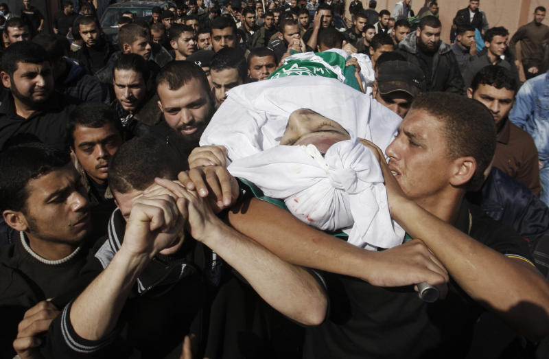 Palestinian mourners carry the body of Hamas militant Mohammed Al Qanoah during his funeral in Gaza City, Tuesday, Nov. 13, 2012. A Palestinian health official said Al Qanoah has died of wounds sustained in an Israeli airstrike on Saturday, Nov. 10, 2012. His death brings to seven the number of Gazans killed in Israeli airstrikes since Saturday. (AP Photo/Hatem Moussa)