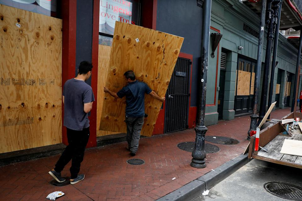 Men place plywood in front of a store in preparation for Hurricane Ida, in New Orleans (REUTERS)