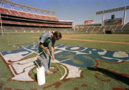 FILE - In this October 1984 file photo, a groundskeeper at Jack Murphy Stadium paints the logo for the 1984 World Series between San Diego Padres and Detroit Tigers in San Diego. The biggest piece of San Diego's sports history is slowly being knocked down and ground to bits. Now the stadium is coming to an unceremonious end, leaving generations of fans feeling melancholy because, due to the coronavirus pandemic, they didn't get to say a proper goodbye to the place where they tailgated with gusto in the massive parking lot before cheering on the Chargers, Padres and Aztecs, or watched myriad other events and concerts. (AP Photo,File)