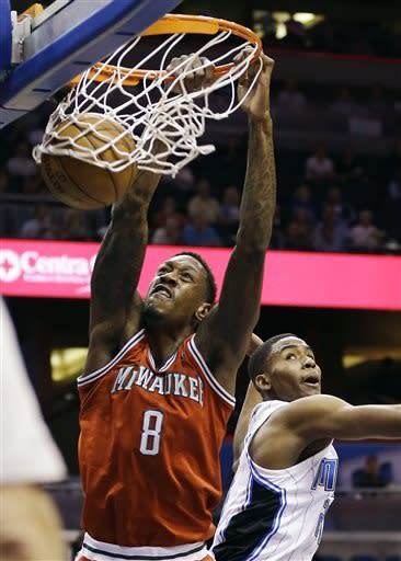 Milwaukee Bucks' Larry Sanders (8) dunks the ball over Orlando Magic's Maurice Harkless during the first half of an NBA basketball game, Wednesday, April 10, 2013, in Orlando, Fla. (AP Photo/John Raoux)