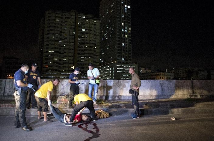 Coroners move the dead body of an alleged drug dealer killed during a police anti-drug operation in Manila on August 18, 2017 (AFP Photo/Noel Celis)