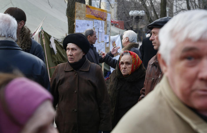 In this photo taken Tuesday, March 11, 2014, men debate as people gather in a pro Russian camp in Luhansk, eastern Ukraine. The breakup of the Soviet Union and harsh economic realities of the market haven't been kind to many local employers. Residents say many factories, including the locomotive works, have had to drastically cut both payrolls and production. Since Russian troops rolled into Crimea, and lawmakers there scheduled a referendum for Sunday on whether to join Russia, the world's attention has focused on the fate of the lush peninsula that juts into the Black Sea. But here in Ukraine's coal-fired industrial east, where Russians have lived for more than two centuries, a potent mix of economic depression, ethnic solidarity and nostalgia for the certainties of the Soviet past have many demanding the right to become part of Russia as well (AP Photo/Sergei Grits)