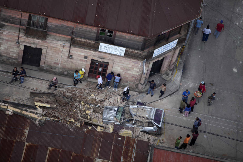 Residents walk around rubble and a car damaged after a magnitude 7.4 earthquake struck in San Marcos, Guatemala, Wednesday Nov. 7, 2012. The mountain village, some 80 miles (130 kilometers) from the epicenter, suffered much of the damage with some 30 homes collapsing in its center. There are three confirmed dead and many missing after the strongest earthquake to hit Guatemala since a deadly 1976 quake that killed 23,000. (AP Photo/Moises Castillo)
