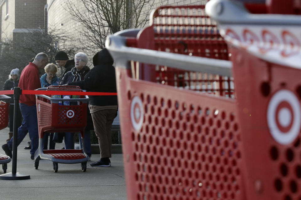 Shoppers wait to enter at a Target store in Glenview, Ill., Wednesday, March 25, 2020. Grocery store chains and other retailers began offering special shopping hours for seniors and other groups considered the most vulnerable to the new coronavirus. The new coronavirus cause mild or moderate symptoms for most people, but for some, especially older adults and people with existing health problems, it can cause more severe illness or death. (AP Photo/Nam Y. Huh)