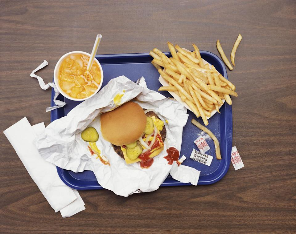 A cheeseburger, fries, and a soda on a tray