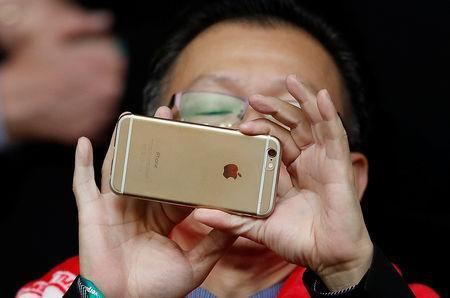 FILE PHOTO: A man uses an Apple iPhone to take photographs before the Liverpool versus Tottenham Hotspur soccer match at Anfield in Liverpool northern England, April 2, 2016. REUTERS/Phil Noble/File Photo