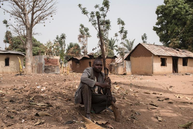 A vigilante sits on the ground with his gun in a village in Kaduna state which was recently attacked by suspected Fulani herdsmen (AFP Photo/STEFAN HEUNIS)