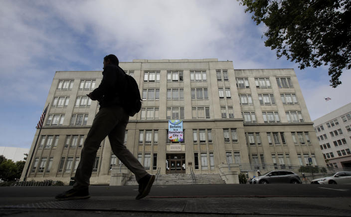 """A man walks past the Martin Luther King Jr. Civic Center building in Berkeley, Calif., Thursday, July 18, 2019. Soon students in Berkeley, California will have to pledge to """"collegiate Greek system residences"""" instead of sororities or fraternities and city workers will have to refer to manholes as """"maintenance holes."""" Berkeley leaders voted unanimously this week to replace about 40 gender-specific words in the city code with gender-neutral terms. (AP Photo/Jeff Chiu)"""