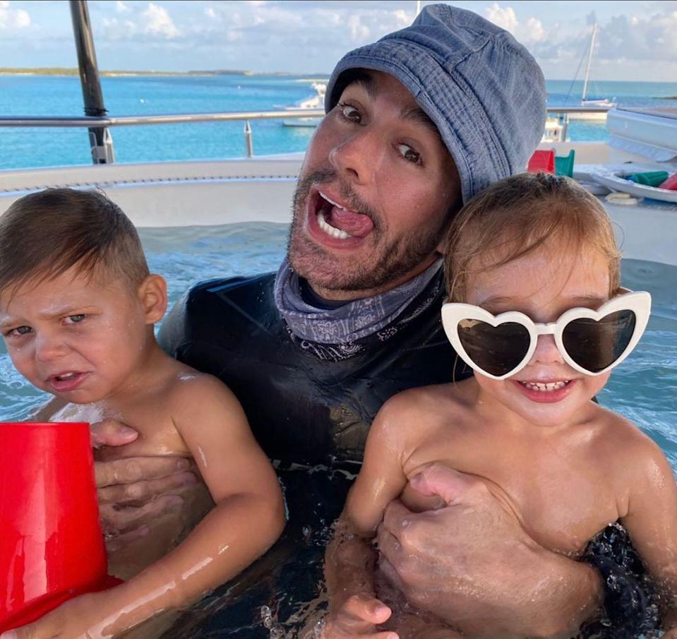 """<p><a href=""""https://people.com/parents/enrique-iglesias-shares-silly-photo-with-twins-lucy-and-nicholas-on-fourth-of-july/"""" rel=""""nofollow noopener"""" target=""""_blank"""" data-ylk=""""slk:On July 4, 2021"""" class=""""link rapid-noclick-resp"""">On July 4, 2021</a>, Iglesias held his twins in each of his arms as he poked his tongue out and made a silly face at the camera. Nicholas didn't appear as enthused to take the photo whereas Lucy shared a big smile while wearing heart-shaped sunglasses.</p> <p>""""#MEPASE 🤪 #fourthofjuly,"""" the singer captioned the photo. """"Me Pasé"""" refers to his newly released single — his first since 2019.</p>"""