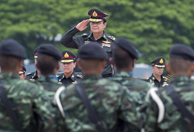 Thai Army Chief Prayut Chan-O-Cha (C) salutes while reviewing a guard of honour as part of the military anniversary at 21st Infantry Regiment in Chonburi province on August 21, 2014 (AFP Photo/Pornchai Kittiwongsakul)