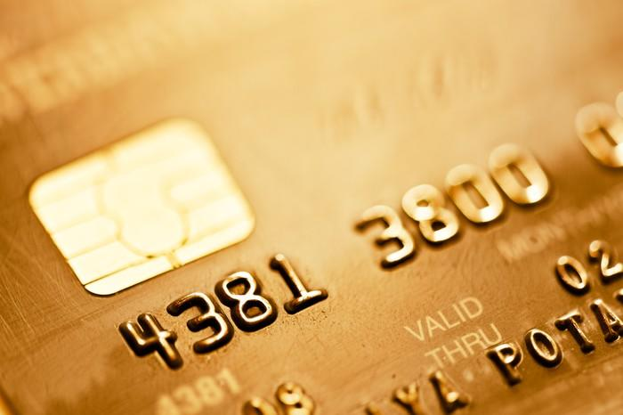 Close-up of a gold-colored credit card showing part of the number and the EMV chip.