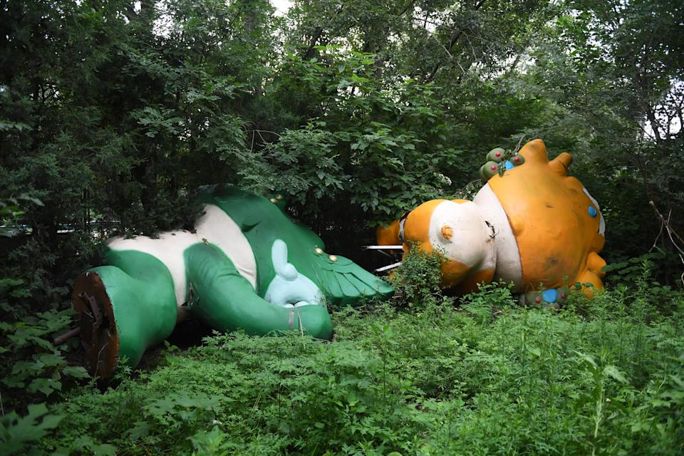 TOPSHOT - This photo taken on July 20, 2018 shows Nini (L) and Yingying, two of the five mascots for the 2008 Beijing Olympic Games, lying among trees behind an abandoned, never-completed mall in Beijing. - A decade after Beijing hosted the 2008 Olympics, its legacy remains unmistakable from the smallest alleyways in the Chinese capital to the country's growing clout abroad. For better or worse, the Games changed the face of Beijing: from the iconic Bird's Nest stadium to the countless blocks of ancient homes bulldozed in an Olympic building frenzy. (Photo by GREG BAKER / AFP) / TO GO WITH China-politics-Olympics-anniversary,FOCUS by Ben Dooley        (Photo credit should read GREG BAKER/AFP via Getty Images)