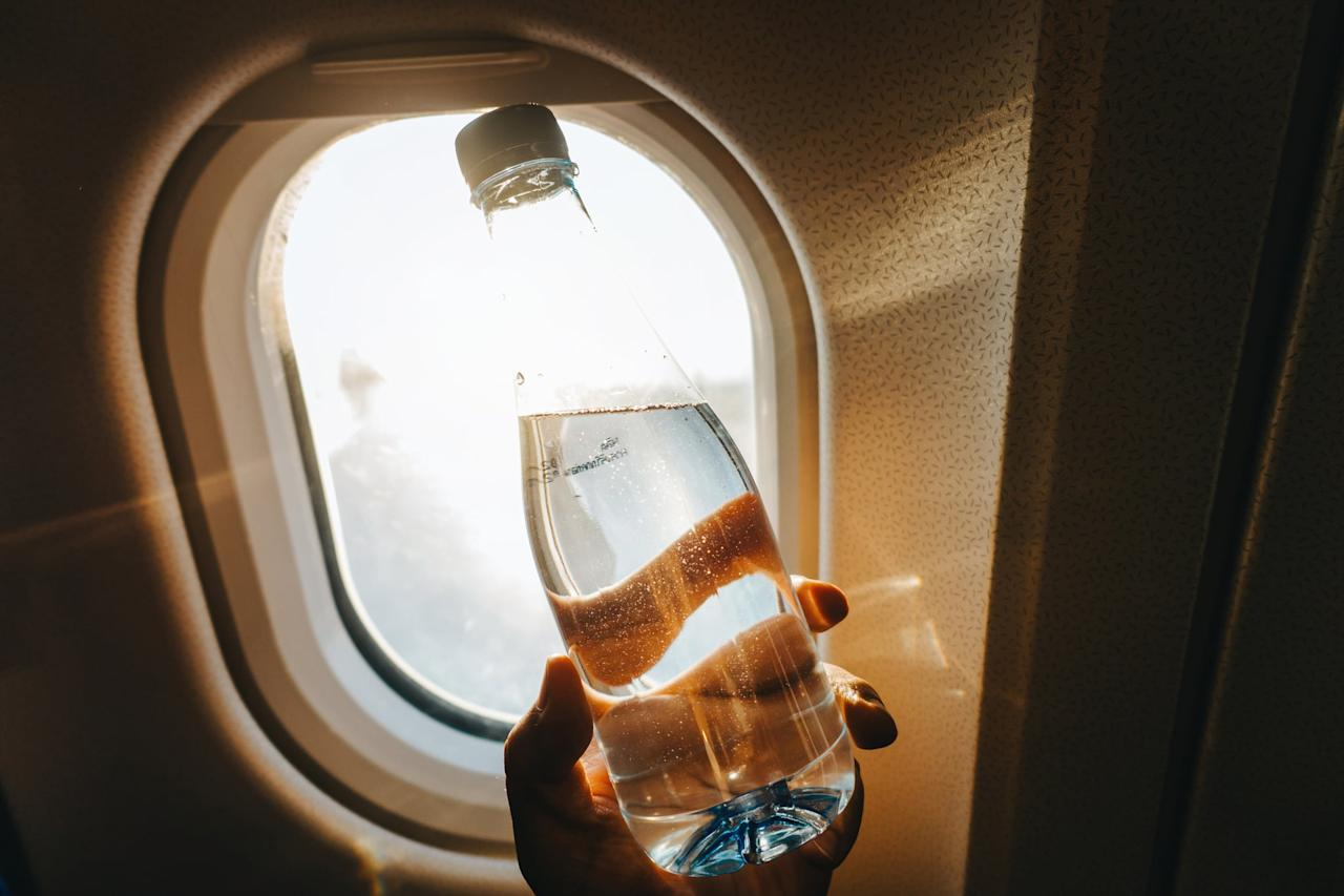 """<p>Sure, it might not technically be food, but water is perhaps the most important item on this list. Flying can severely dehydrate you due to low humidity levels in the cabin, so it's vital to increase your water intake. """"Drinking lots of water prevents bloating, headache, and fatigue,"""" <a href=""""http://www.mediaambassadors.com/mimi-secor"""" target=""""_blank"""" class=""""ga-track"""" data-ga-category=""""Related"""" data-ga-label=""""http://www.mediaambassadors.com/mimi-secor"""" data-ga-action=""""In-Line Links"""">Mimi Secor</a>, DNP, co-founder of the health and fitness program <a href=""""http://www.coachkatanddrmimi.com"""" target=""""_blank"""" class=""""ga-track"""" data-ga-category=""""Related"""" data-ga-label=""""http://www.coachkatanddrmimi.com"""" data-ga-action=""""In-Line Links"""">Coach Kat and Dr. Mimi</a>, told POPSUGAR. """"Also, avoid caffeine and alcohol because both can cause headaches, fatigue, irritability, and contribute to jet lag and poor sleep. If I'm craving alcohol or a soda, I order club soda with lemon or lime.""""</p> <p><a href=""""http://www.drharrymd.com/"""" target=""""_blank"""" class=""""ga-track"""" data-ga-category=""""Related"""" data-ga-label=""""http://www.drharrymd.com/"""" data-ga-action=""""In-Line Links"""">Eudene Harry</a>, MD, medical director of <a href=""""http://www.md.com/doctor/eudene-harry-md#office-193719"""" target=""""_blank"""" class=""""ga-track"""" data-ga-category=""""Related"""" data-ga-label=""""http://www.md.com/doctor/eudene-harry-md#office-193719"""" data-ga-action=""""In-Line Links"""">Oasis Wellness and Rejuvenation Center</a>, recommends coconut water for best results. """"Coconut water provides double the benefits: hydration and high potassium,"""" she explained. """"Both hydration and potassium help keep muscles from cramping and your energy level up.""""</p> <p>So, how much should you drink? The Aerospace Medical Association recommends <a href=""""http://www.asma.org/asma/media/asma/Travel-Publications/HEALTH-TIPS-FOR-AIRLINE-TRAVEL-Trifold-2013.pdf"""" target=""""_blank"""" class=""""ga-track"""" data-ga-category=""""Related"""" data-ga-label=""""http://www.asma.org/asma/m"""