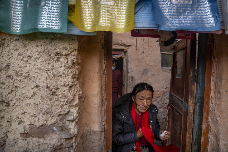 A Tibetan man leaves a Buddhist holy site built in a grotto in Namtso in western China's Tibet Autonomous Region, Wednesday, June 2, 2021, as seen during a government organized visit for foreign journalists. High-pressure tactics employed by China's ruling Communist Party appear to be finding success in separating Tibetans from their traditional Buddhist culture and the influence of the Dalai Lama. (AP Photo/Mark Schiefelbein)