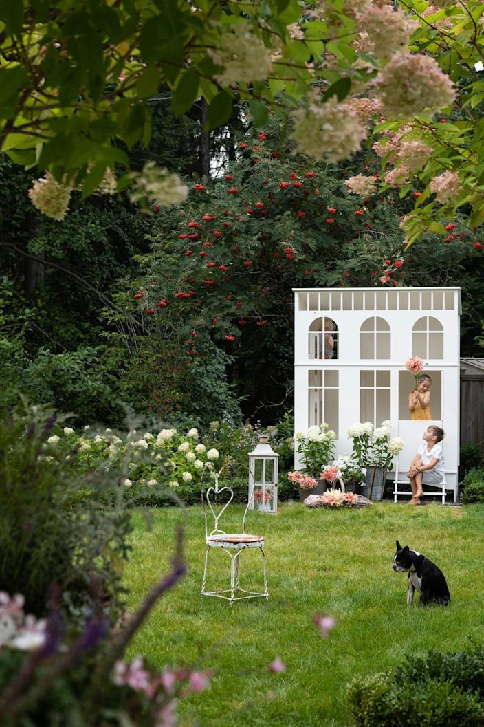 The Joneses' stunning yard (which was designed by landscape architects from Cyan Horticulture) features an antique chair from Southlands Nursery, a lantern from RH, and a custom playhouse from Conifer Toys.