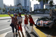 Supporters of President Donald Trump pose for a selfie in front of a Lamborghini decorated with an image of the president, as they arrive for a campaign event with Ivanka Trump at Bayfront Park Amphitheater, in Miami, Tuesday, Oct. 27, 2020. (AP Photo/Rebecca Blackwell)