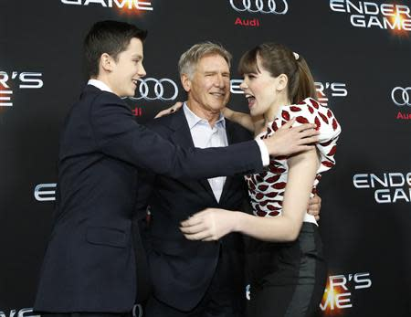 """Cast members Asa Butterfield (L), Hailee Steinfeld (R) and Harrison Ford greet each other at the premiere of """"Ender's Game"""" at the TCL Chinese theatre in Hollywood, California October 28, 2013. REUTERS/Mario Anzuoni"""