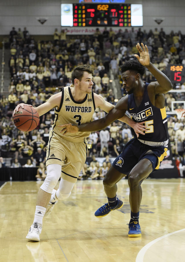 Wofford guard Fletcher Magee (3) tries to control the ball against UNC-Greensboro forward Khyre Thompson (15) in the first half of an NCAA college basketball game for the Southern Conference tournament championship, Monday, March 11, 2019, in Asheville, N.C. (AP Photo/Kathy Kmonicek)