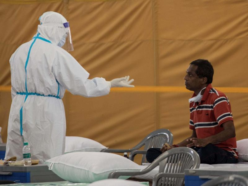 A health worker in India talks to a coronavirus patient in India: AFP via Getty Images