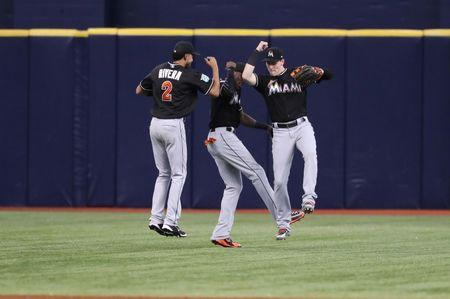 Jul 21, 2018; St. Petersburg, FL, USA; Miami Marlins left fielder Yadiel Rivera (2), center fielder Cameron Maybin (1) and right fielder Brian Anderson (15) congratulate each other as they best the Tampa Bay Rays at Tropicana Field. Mandatory Credit: Kim Klement-USA TODAY Sports