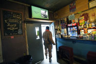 "A customer walks out of the Blue Front Cafe in Bentonia, Miss., while a YouTube video of owner and bluesman Jimmy ""Duck"" Holmes plays on the television set, Jan. 21, 2021. The cafe is among the oldest surviving juke joints in the state, having been founded by Holmes parents. (AP Photo/Rogelio V. Solis)"